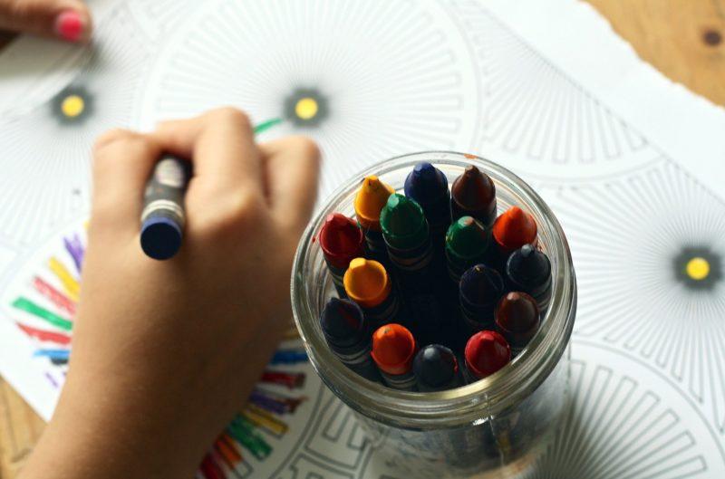 Widok dziecięcej ręki rysującej kredką na kartce obok stoi słoik z kredkami